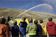 A group of adults watching firemen spray a water hose from a fire truck.