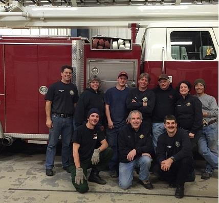 A group of firefighters standing in front of a fire truck.