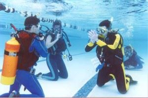 Two adults taking scuba classes in a pool.