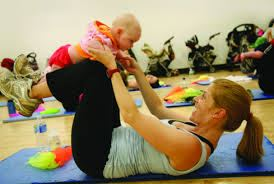 A woman working out while holding her baby.