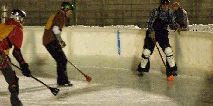 Adults playing broomball on a hockey rink.