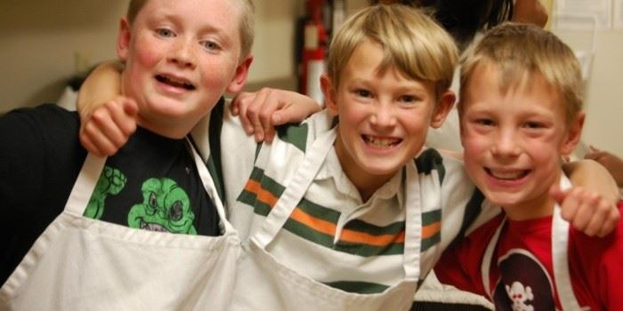 Three boys in aprons standing together.
